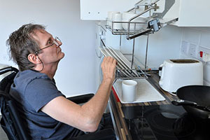 accessible housing - a man in a wheelchair uses accessible kitchen