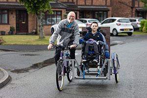 An older man on an Insync Bike and young boy on special needs trike