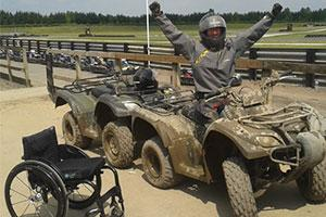 Sportability a muddy quadbike rider and wheelchair
