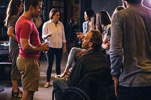 A group of people from an inclusive company - one with a disability - drinking and talking